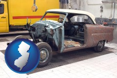 new-jersey map icon and a vintage automobile in an auto body shop