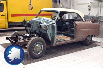 a vintage automobile in an auto body shop - with Alaska icon