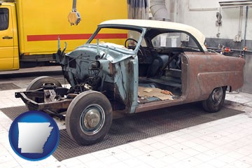 a vintage automobile in an auto body shop - with Arkansas icon