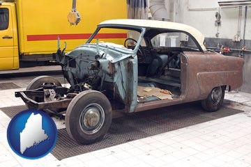a vintage automobile in an auto body shop - with Maine icon