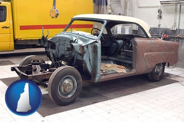 a vintage automobile in an auto body shop - with New Hampshire icon