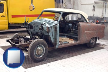 a vintage automobile in an auto body shop - with New Mexico icon